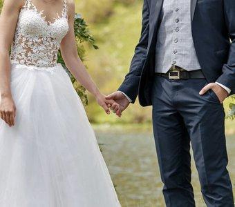 387e0c8b8cc88d Ein Brautpaar posiert händehaltend